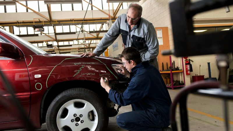A specialist outlining the damaged area during fender repair at the car body shop