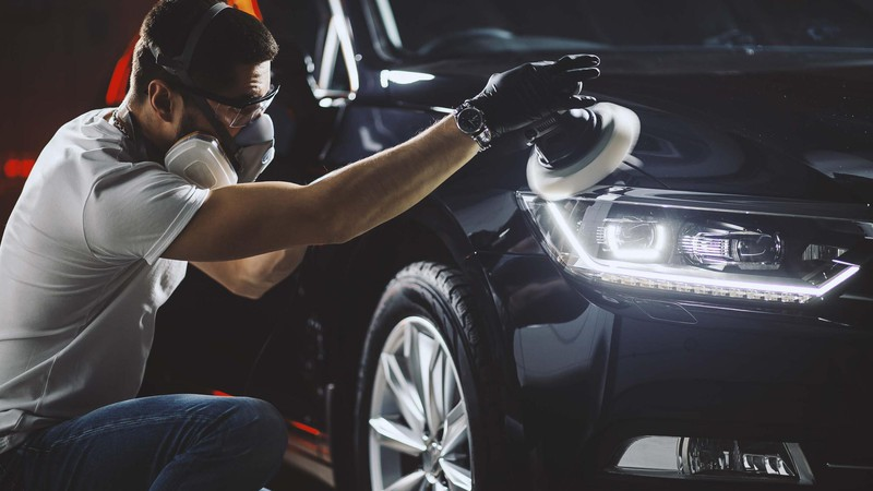 A man polishing a car body after front fender repair